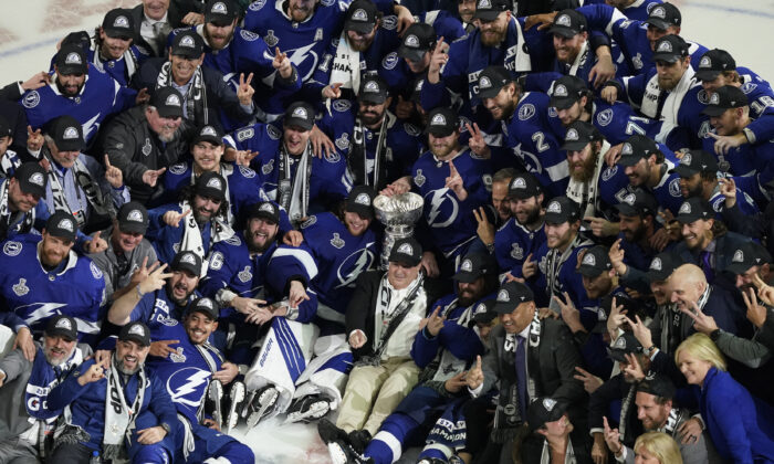 The Tampa Bay Lightning team poses with the Stanley Cup after Game 5 of the NHL hockey Stanley Cup finals against the Montreal Canadiens, in Tampa, Fla., on July 7, 2021. (Gerry Broome/AP Photo)
