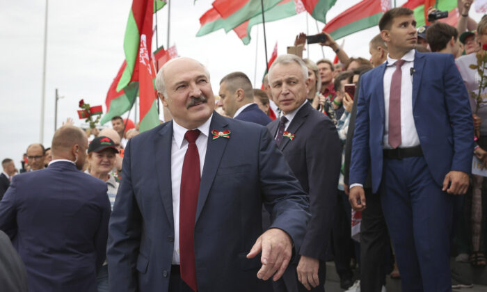 Belarusian President Alexander Lukashenko speaks with people after the wreath laying ceremony at Mound of Glory war memorial marking Independence Day, on the outskirts of the capital Minsk, Belarus, on July 3, 2021. (Maxim Guchek/BelTA Pool Photo via AP)