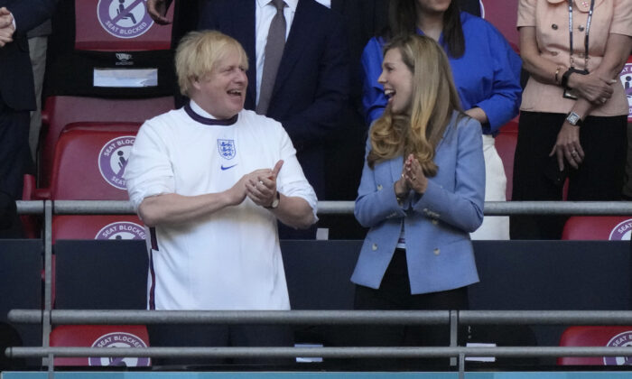 Boris Johnson, Prime Minister of United Kingdom and his wife, Carrie Johnson react prior to the UEFA Euro 2020 Championship Semifinal match between England and Denmark at Wembley Stadium in London on July 7, 2021. (Frank Augstein/Pool/Getty Images)