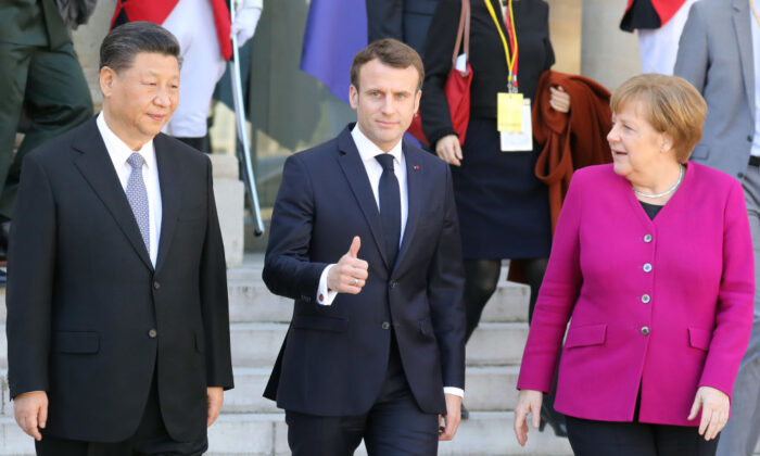 French President Emmanuel Macron (C) gestures next to German Chancellor Angela Merkel (R) and Chinese leader Xi Jinping (L) following their meeting at the Elysee Palace in Paris on March 26, 2019. (LUDOVIC MARIN/AFP via Getty Images)