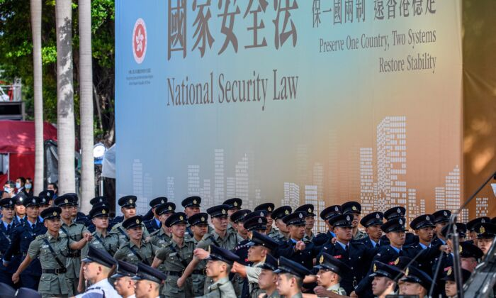 Attendees from various forces march next to a banner supporting the new national security law at the end of a flag-raising ceremony to mark the 23rd anniversary of Hong Kong's handover from Britain in Hong Kong on July 1, 2020. (Anthony Wallace/AFP via Getty Images)
