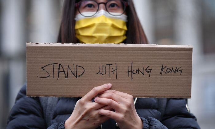 A protester holds a small placard at an event organised by Justitia Hong Kong to mourn the loss of Hong Kong's political freedoms, in Leicester Square, central London on Dec. 12, 2020. (Justin Tallis/AFP via Getty Images)