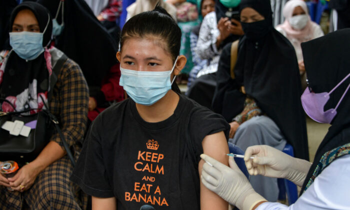 A woman receives a dose of Sinovac's Covid-19 coronavirus vaccine during a vaccination drive in Banda Aceh, Indonesia on July 7, 2021. (Chaideer Mahyuddin/AFP via Getty Images)