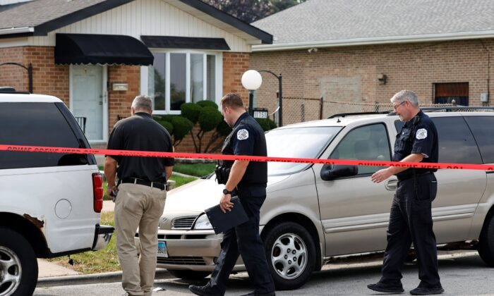Law enforcement officers investigate a crime scene near the border between the Morgan Park and West Pullman neighborhoods in Chicago, Ill., on July 7, 2021. (Kamil Krzaczynski/Getty Images)