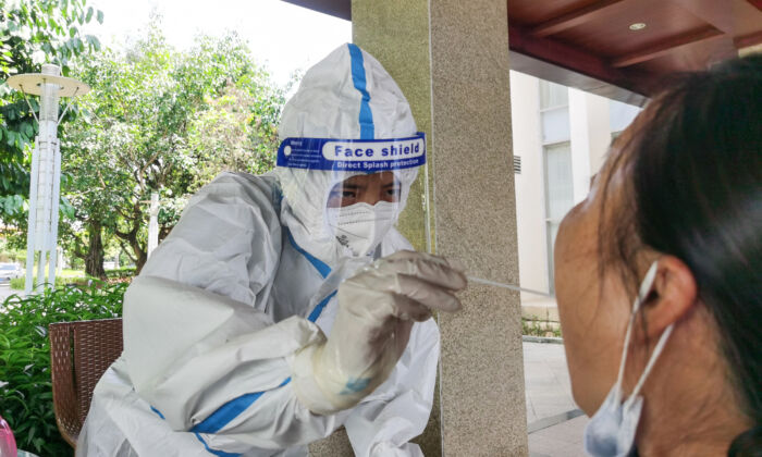A woman (R) being swabbed for nucleic acid testing for the CCP virus at a hotel in the city of Ruili in China's southwestern Yunnan province on July 8, 2021. (STR/AFP via Getty Images)