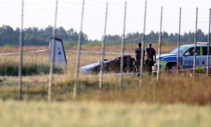 Police officers observe a small aircraft that crashed at Orebro Airport, Orebro, Sweden, on July 8 2021. (TT News Agency/Jeppe Gustafsson via Reuters)
