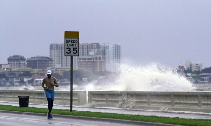 A jogger makes his way along Bayshore Blvd., in Tampa, Fla., as a wave breaks over a seawall, during the aftermath of Tropical Storm Elsa on July 7, 2021. (John Raoux/AP Photo)