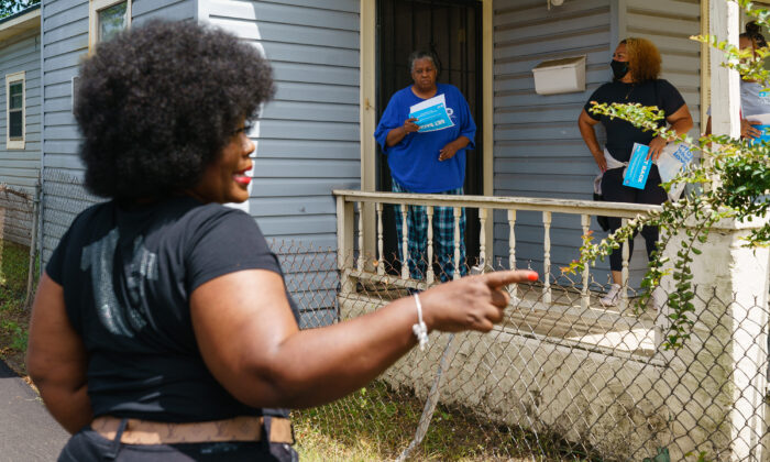 Jefferson County Commissioner Sheila Tyson (L) accompanies volunteers and staffers during a door-knocking outreach effort to inform residents about an upcoming COVID-19 vaccination event in Birmingham, Ala., on June 30, 2021. (Elijah Nouvelage/AFP via Getty Images)