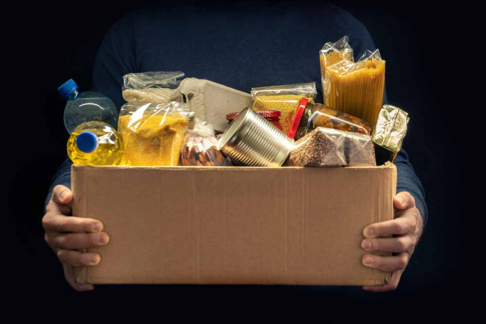 A,Man,Holding,A,Donation,Box,Of,Different,Products,On
