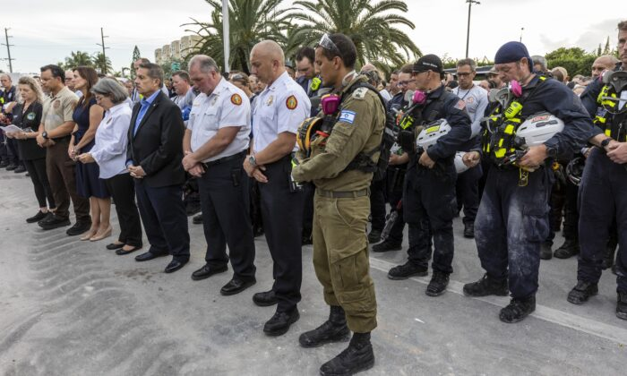 Miami-Dade County officials, members of search and rescue teams and Miami-Dade Fire Rescue along with police and workers who have been working at the site of the collapse, gather for a moment of prayer and silence in front of the rubble at the site of the Champlain Towers South condominium collapse in Surfside, Fla., on July 7, 2021. (Jose A Iglesias/Miami Herald via AP)