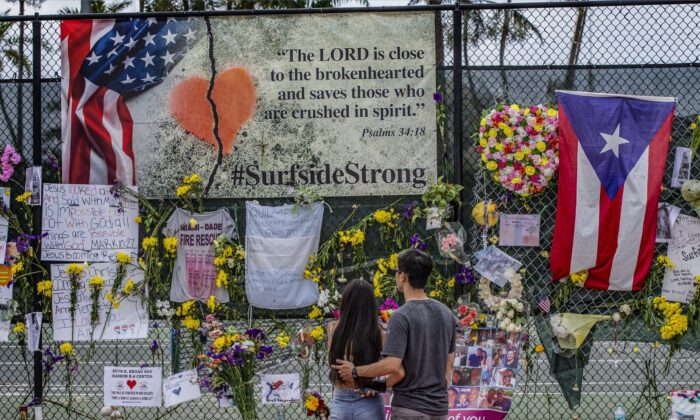 Mementos, personal items, and flowers are seen displayed at the Surfside Wall of Hope Memorial in Surfside, Fla., on July 7, 2021. (Al Diaz/Miami Herald via AP)