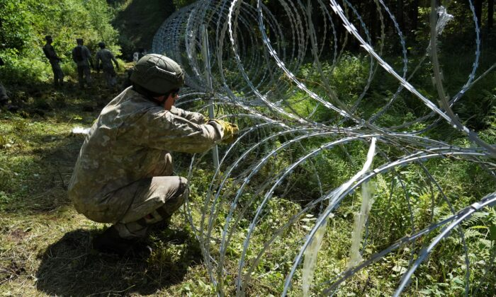 Lithuanian army soldiers install razor wire on border with Belarus in Druskininkai, Lithuania, on July 9, 2021. (Janis Laizans/Reuters)