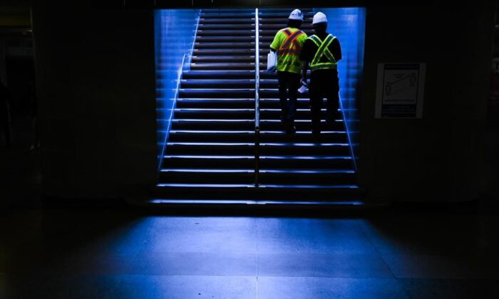 Construction workers walk up a set of stairs at Union Station during the COVID-19 pandemic in Toronto on May 11, 2021. (The Canadian Press/Nathan Denette)