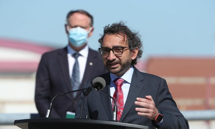 Transport Minister Omar Alghabra speaks while Ottawa South MP David McGuinty looks on during a press conference at the Ottawa MacDonald-Cartier International Airport on June 16, 2021. (The Canadian Press/David Kawai )