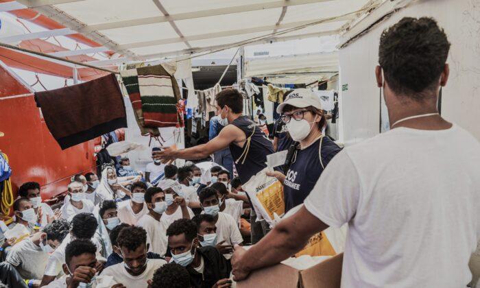 Staffers distribute food to migrants on the deck of the Ocean Viking rescue in the Mediterranean Sea, on July 5, 2021. (Flavio Gasperini/SOS Mediterranee via AP)