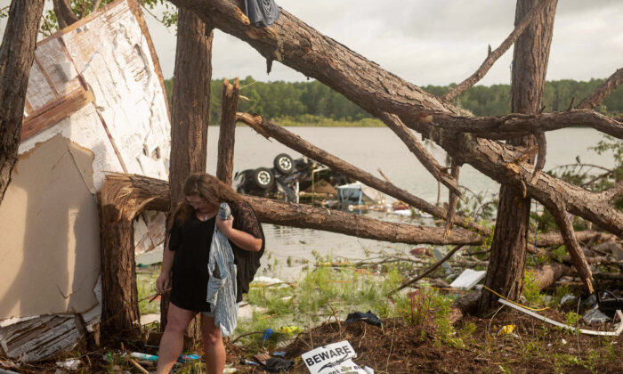 Missy Lattanzie, an RV park resident, searches through her belongings that were destroyed after a tornado touched down Wednesday on Naval Submarine Base Kings Bay in Kings Bay, Ga., on July 8, 2021. (Mass Communication 3rd Class Aaron Xavier Saldana/U.S. Navy via AP)