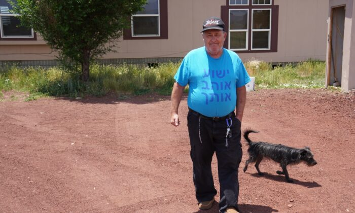 Daniel J. Miller, 61, of Parks, Ariz., and his dog Buddy go for a walk on July 8 in front of their house. Miller said he won't take the COVID-19 vaccine even if federal employees come knocking at his door.    (Allan Stein/The Epoch Times)