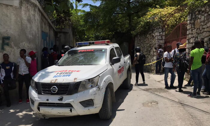People stand next to a police car and a yellow police cordon near the residence of Haiti's President Jovenel Moise after he was shot dead by unidentified attackers, in Port-au-Prince, Haiti, on July 7, 2021. (Estailove St-Val/Reuters)