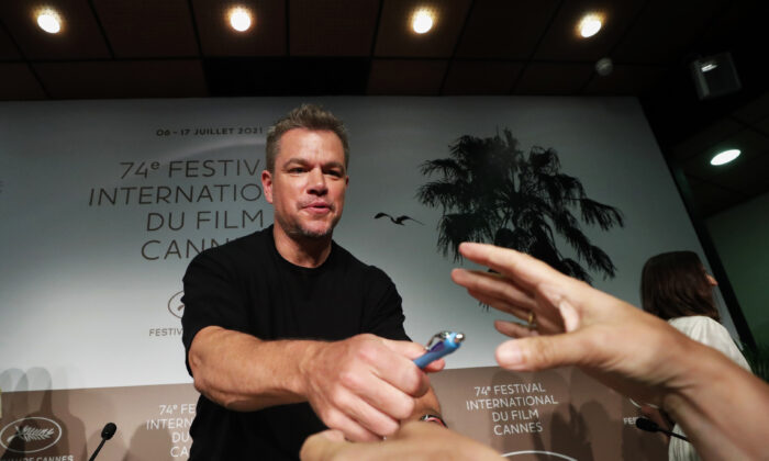 """Cast member Matt Damon signs autographs at a press conference for the film """"Stillwater"""" at the 74th Cannes Film Festival in Cannes, France, on July 9, 2021. (Eric Gaillard/Reuters)"""