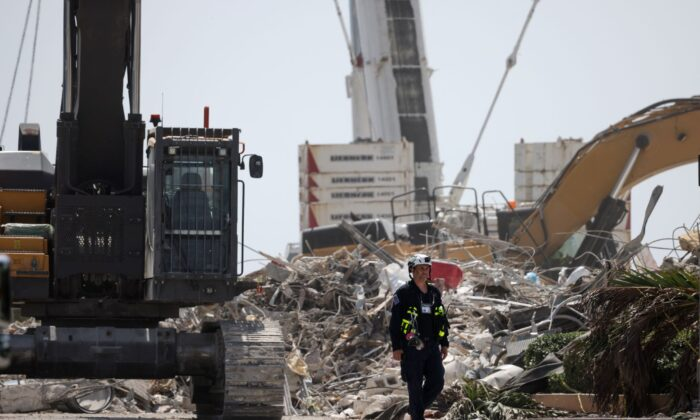A rescue worker walks away from the remains of the collapsed 12-story Champlain Towers South condo building in Surfside, Fla., on July 08, 2021. (Anna Moneymaker/Getty Images)
