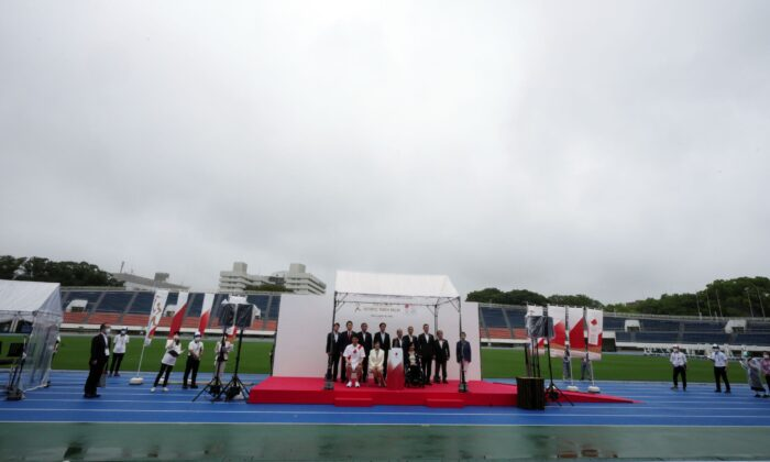 Guests pose for photographers during the unveiling ceremony for Olympic Flame of the Tokyo 2020 Olympic torch relay at empty Komazawa Olympic Park, in Tokyo, Japan,  on July 9, 2021. (Eugene Hoshiko/AP Photo)