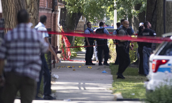 Police investigate the scene in which police opened fire during an arrest near 109 S Kilpatrick in West Garfield Park in Chicago, Ill., on July 9, 2021. (Anthony Vazquez/Chicago Sun-Times via AP)