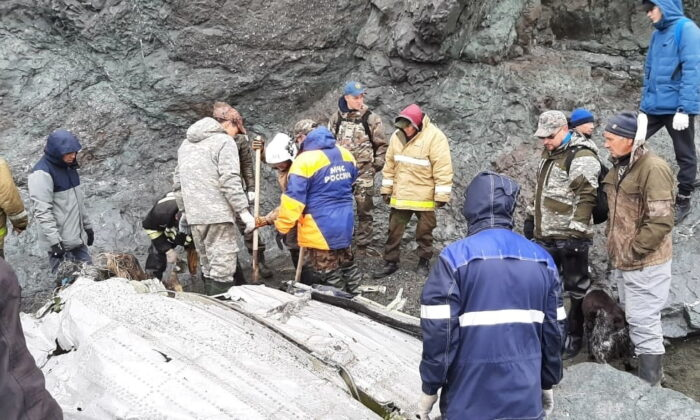 Specialists of the Russian Emergencies Ministry are seen at the crash site of a Russian An-26 passenger plane near the village of Palana in the north of the Kamchatka peninsula, Russia, on July 7, 2021. (Russia's Emergencies Ministry/Handout via Reuters)