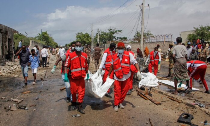 Medical workers carry the body of a civilian who was killed in a suicide car bomb attack that targeted the city's police commissioner in Mogadishu, Somalia, on July 10, 2021. (Farah Abdi Warsameh/AP Photo)