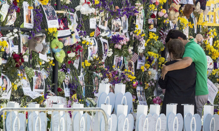 People mourn at the memorial wall for the victims of the Champlain Towers South collapse, in Surfside, Fla., on July 8, 2021. (Pedro Portal/Miami Herald via AP)