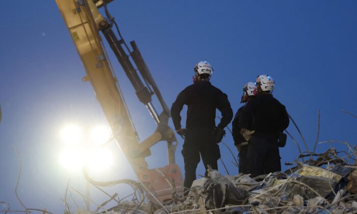 Search and rescue workers oversee an excavator dig through the rubble of the collapsed 12-story Champlain Towers South condo building in Surfside, Florida on July 9, 2021. (Anna Moneymaker/Getty Images)