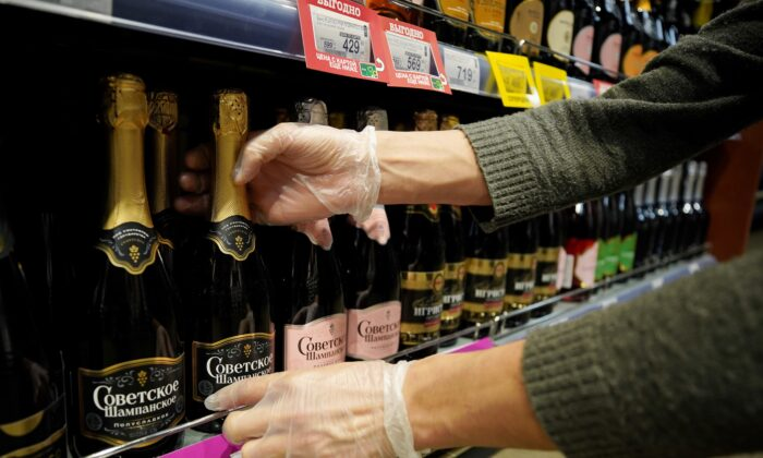 An employee arranges bottles of Russian sparkling wine at a supermarket in Moscow on July 5, 2021. (Tatyana Makeyeva/Reuters)