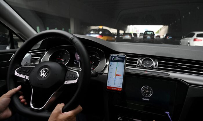 A driver uses the map on the DiDi Chuxing ride-hailing app on his smartphone while driving on a street in Beijing on July 5, 2021. (GREG BAKER/AFP via Getty Images)