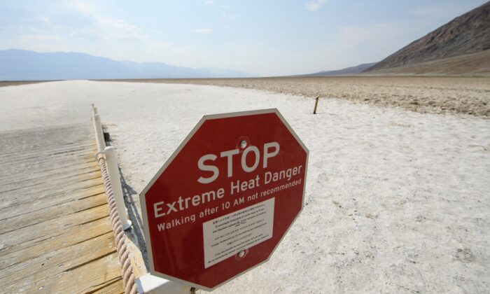 Signage warns of extreme heat danger at the salt flats of Badwater Basin inside Death Valley National Park, in Inyo County, Calif., on June 17, 2021. (Patrick T. Fallon/AFP via Getty Images)