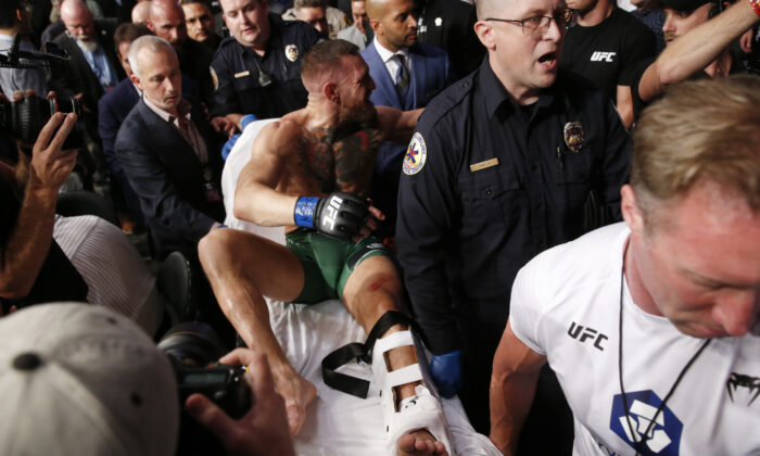 Conor McGregor is stretchered from the octagon after snapping his ankle in a fight with Dustin Poirier during UFC264 at T-Mobile Arena, Las Vegas, on July 10, 2021. (Steve Marcus/Reuters)
