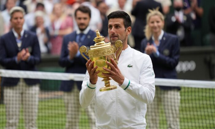 Serbia's Novak Djokovic celebrates holds his winner's trophy and celebrates his victory over Italy's Matteo Berrettini during the men's singles final match on day thirteen of the Wimbledon Tennis Championships in London, England, on July 11, 2021. (Alberto Pezzali/AP Photo)