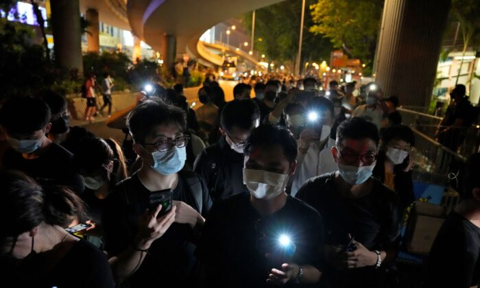 People hold LED candles to mark the anniversary of the military crackdown on a pro-democracy student movement in Beijing, outside Victoria Park in Hong Kong, on June 4, 2021. (Kin Cheung/File/AP Photo)