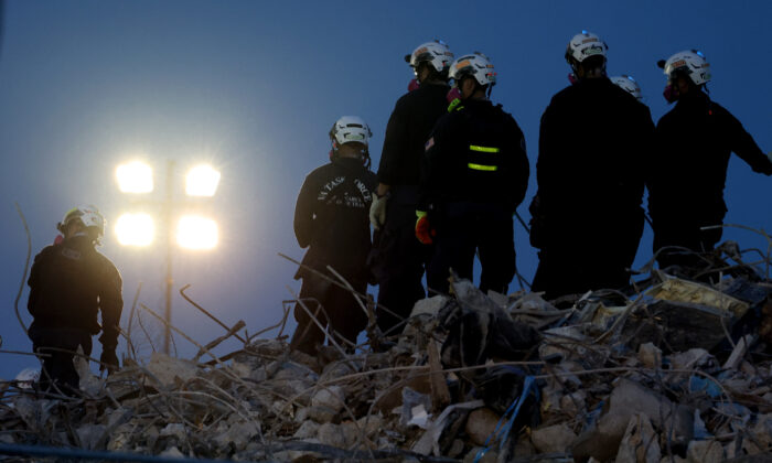Search and rescue workers oversee an excavator dig through the rubble of the collapsed 12-story Champlain Towers South condo building in Surfside, Fla., on July 9, 2021. (Anna Moneymaker/Getty Images)