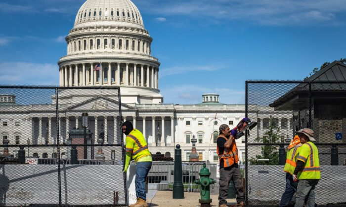 Workers remove security fencing surrounding the U.S. Capitol in Washington, on July 10, 2021. (Drew Angerer/Getty Images)