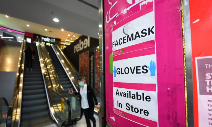 Signage for facemarks and gloves are seen at an entrance to a Priceline Pharmacy in Melbourne, Australia on July 20, 2020. (AAP Image/James Ross)