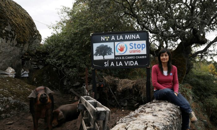 """Raquel Romo, 44, a member of the """"Stop Uranium"""" group, poses near a sign that reads """"Stop Uranium. No to the mine, yes to life"""" outside her parent's house near the site of a planned open-cast uranium mine by Australian mining company Berkeley Energia in the village of Retortillo, near Salamanca, Spain, on Oct. 17, 2018.  (Susana Vera/Reuters)"""