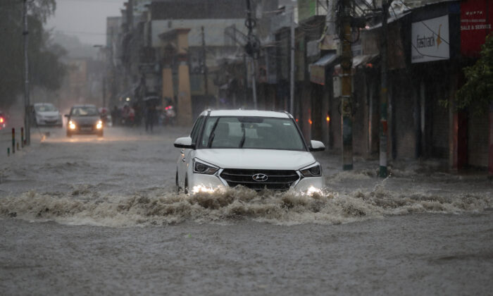 Vehicles move through a flooded road after a heavy rainfall in Jammu, India, Monday, July 12, 2021. (AP Photo/Channi Anand)