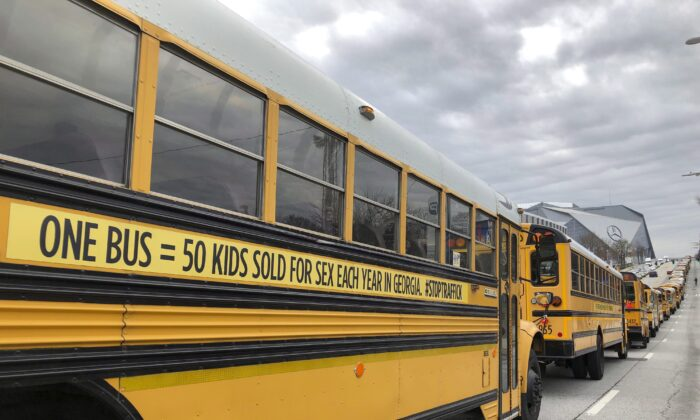 A line of school buses with decals to draw attention to human trafficking make their way along a road in Atlanta, Georgia, on Jan. 2, 2019. (AP Photo/Sarah Morgan)