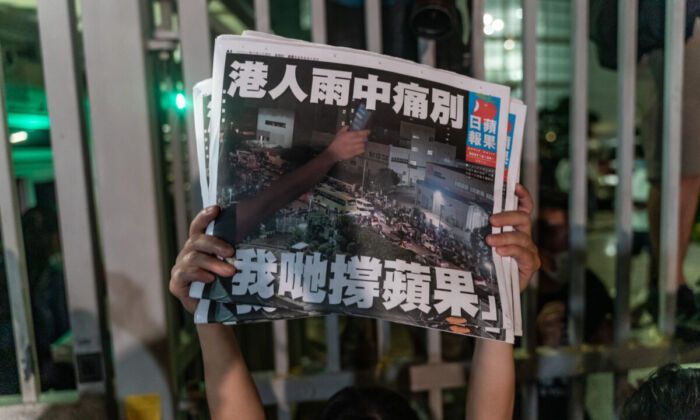 An employee holds up the latest copies of the Apple Daily newspaper outside at the offices in Hong Kong,  on June 24, 2021. (Anthony Kwan/Getty Images)