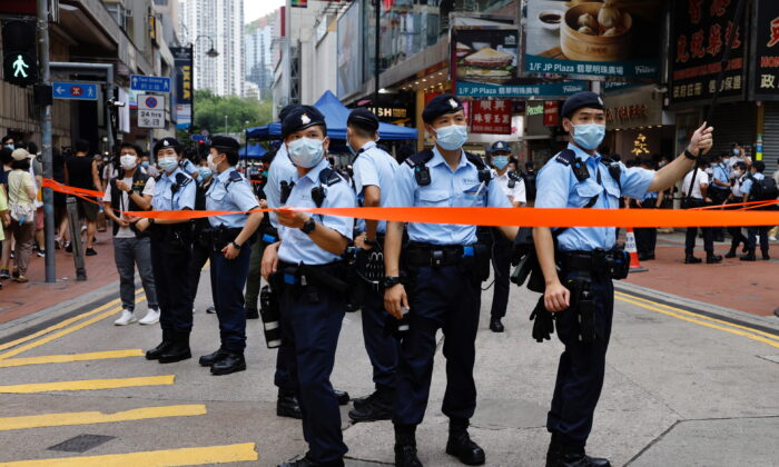 Police stand guard at Causeway Bay in Hong Kong, on July 1, 2021. (Tyrone Siu/Reuters)