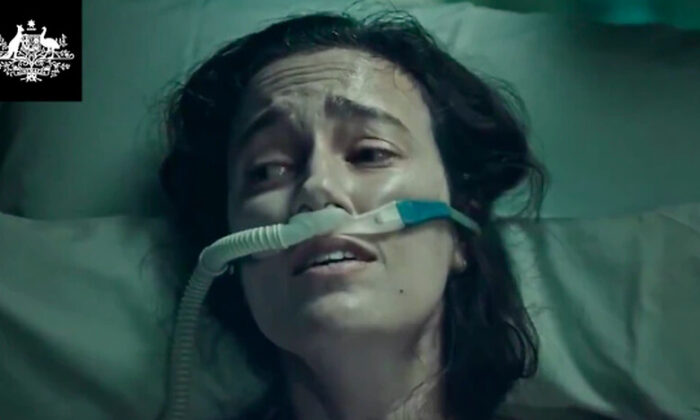 The federal government's new Covid ad depicts a young women struggling to breathe on a hospital bed (Screenshot).