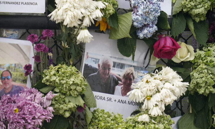 A memorial wall for the victims of the Champlain Towers South building collapse in Surfside, Fla., with a photo of Juan Mora Sr. and his wife, Ana Mora, on June 29, 2021. (Gerald Herbert/AP Photo)