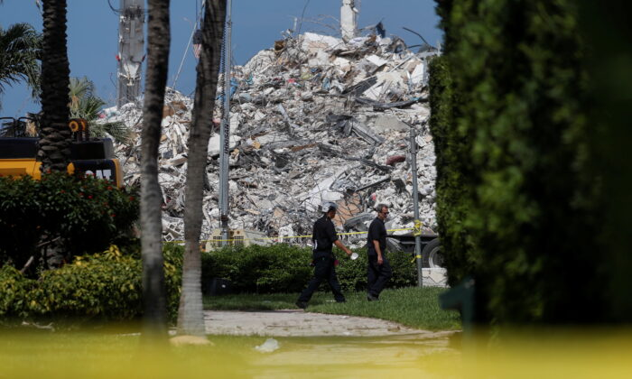 Search teams walk by the remains of the Surfside's Champlain Towers South condominium in Miami on July 8, 2021. (Shannon Stapleton/Reuters)