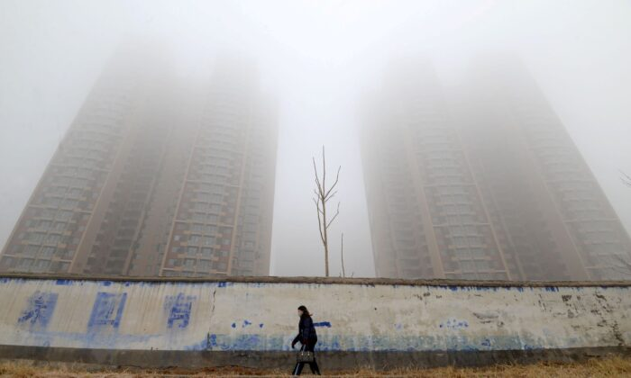 A woman wearing a mask walks past buildings on a polluted day in Handan, Hebei province, China, on Jan. 12, 2019. (Stringer/Reuters)