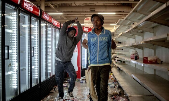 The owner of a shop (L) beats a suspected looter in a shop in Bara Mall, Soweto on July 13, 2021.  (Luca Sola/AFP via Getty Images)