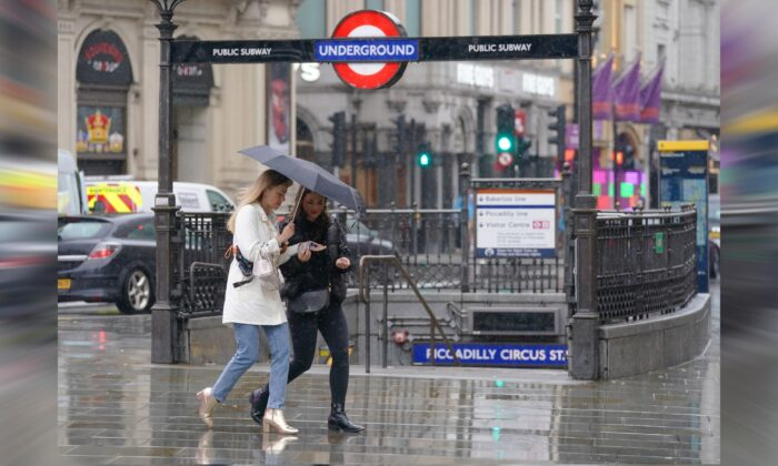 Friends share hand gel as they walk past the entrance to Piccadilly Underground station, London, on June 18, 2021. (Jonathan Brady/PA)